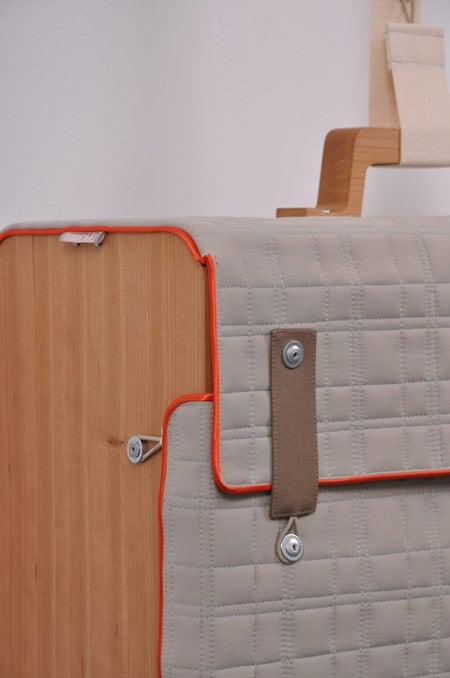 ...чемоданы разных форм, размеров и расцветок, подвешенные на пластиковых лентах к деревянной
