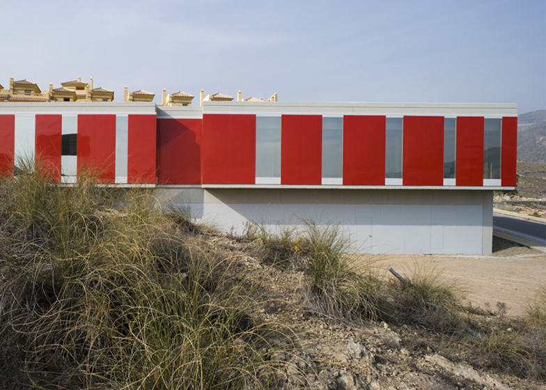 The red panels of this health centre contrast with the earthy tones of the surrounding architecture and the Sierra de Gardor mountains