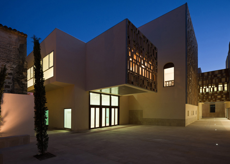 Timber shades shield the upper windows of this extension to a town hall and former prison in the World Heritage town of Baeza