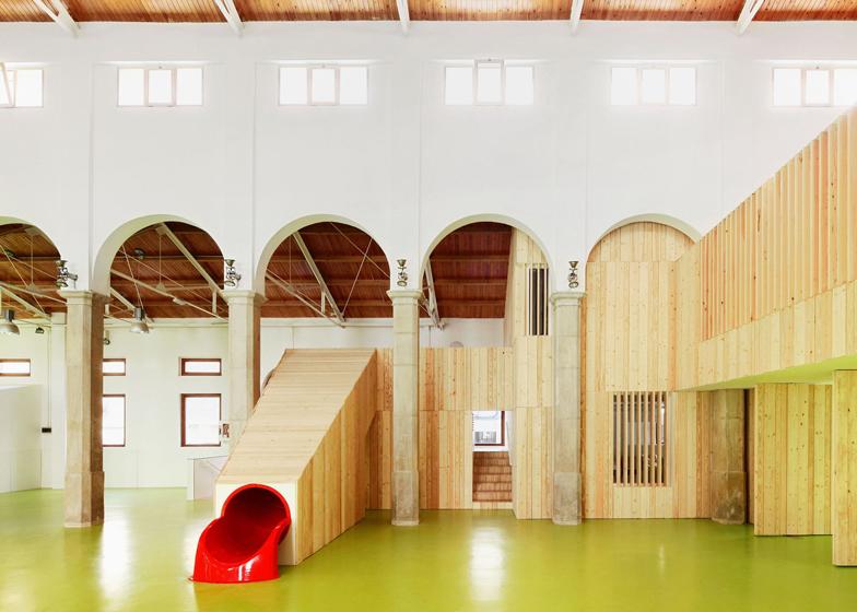 A slide connects two floors of this children's centre by Miquel Mariné Núñez and César Rueda Boné
