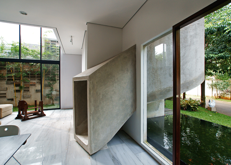 The kitchen and child's bedroom of this house by Aboday near Jakarta are linked by a spiralling concrete slide