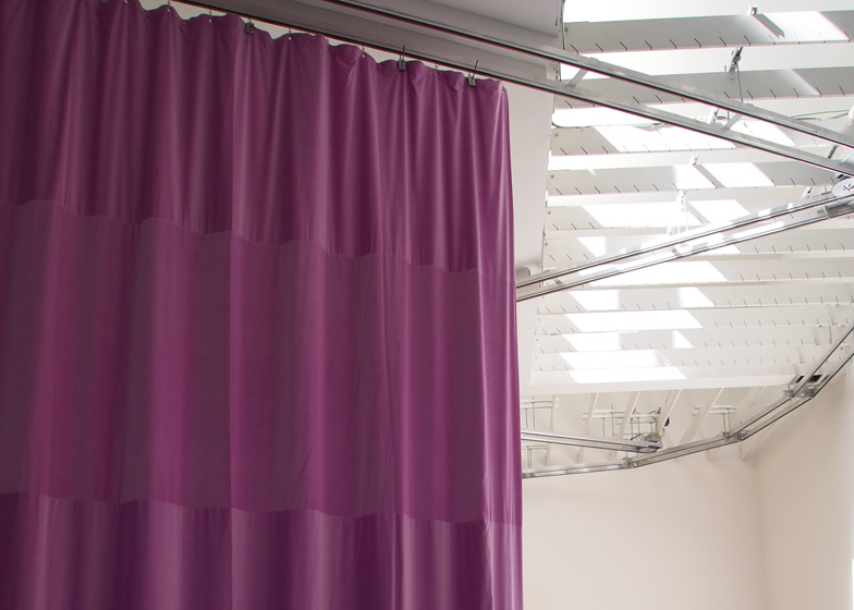 The curtains are attached to a system of motorised cogs that feed them around tracks on the ceiling