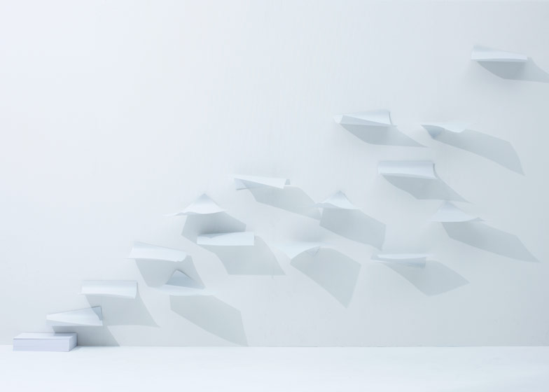 Shelves that look like paper caught in a gust of wind by Japanese studio YOY.
