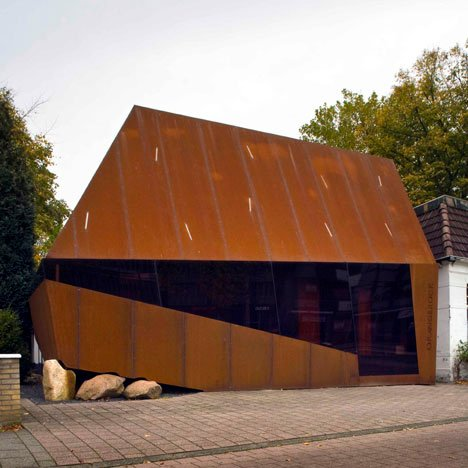 Angular rusted-steel facade wrapped round an old house in a rural town by Möhn + Bouman