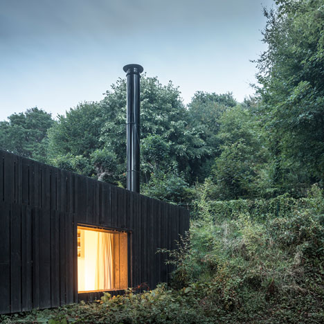 Blackened timber house extension hidden in the forest by Marchi Architectes