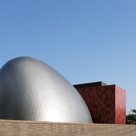 Blob-shaped silver building contrasts with a red tower at Japanese music college