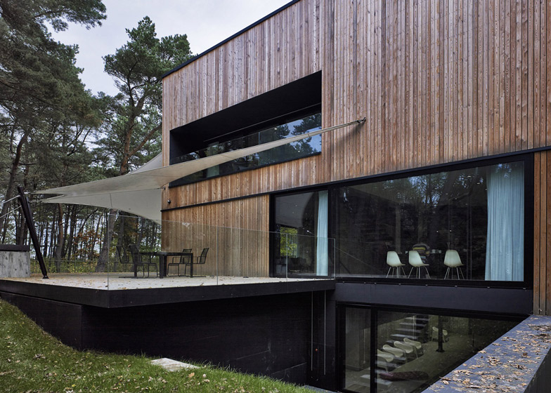 Timber-clad seaside house with a grainy concrete interior by Ultra Architects