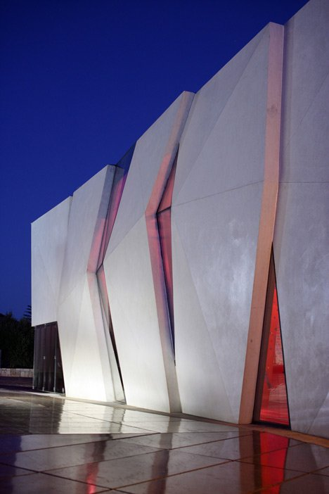 Concrete-clad sports hall by Idis Turato with both faceted and bumpy facades