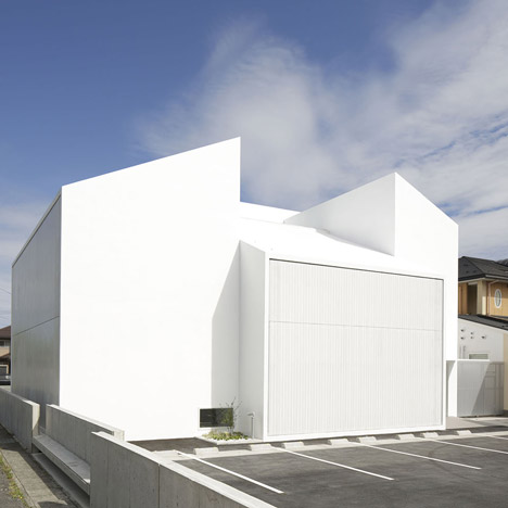 Bright white clinic by Ryutaro Matsuura with concealed windows and patios