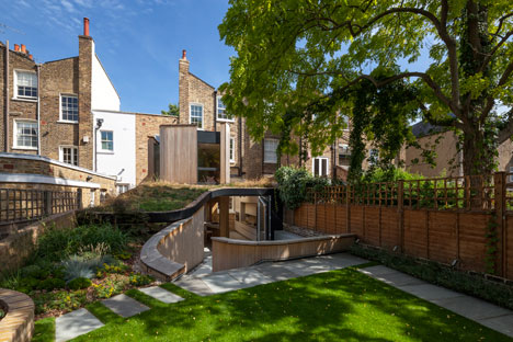 Curvy timber extension by Scott Architects features a sloping grass roof