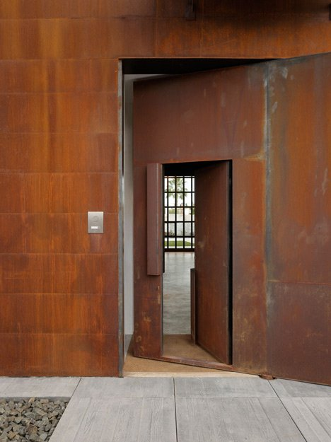 Pivoting steel doors lead into Studio Sitges, a house and photography studio in Spain by Olson Kundig
