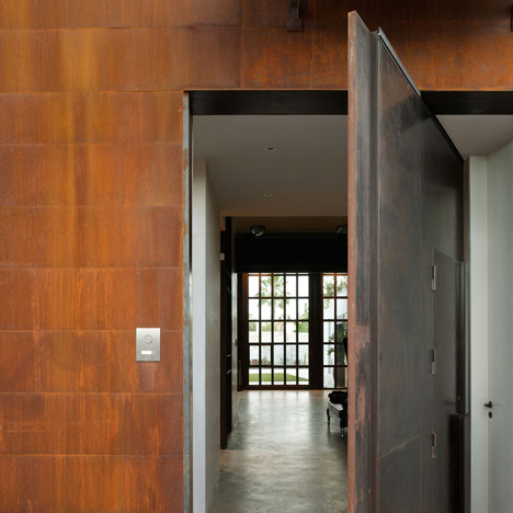 Pivoting steel doors lead into a house and photography studio by Olson Kundig