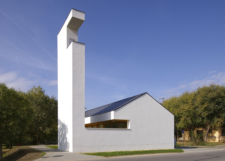 Church congregation hall by SAGRA Architects features a towering white bell tower