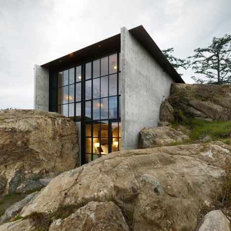 Concrete house by Olson Kundig Architects cut into a rocky outcrop