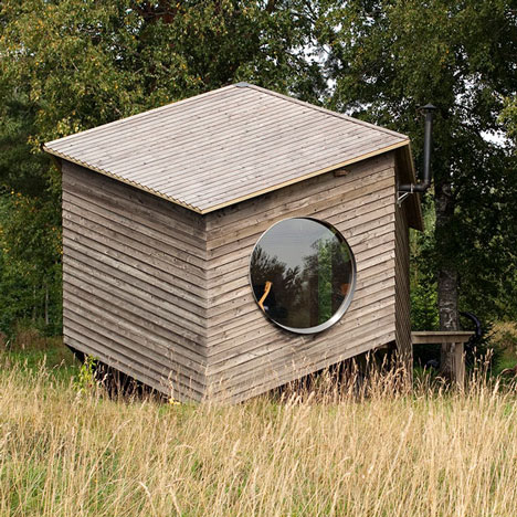 Six-sided modular cabin by Jaanus Orgusaar with wooden walls and fisheye windows