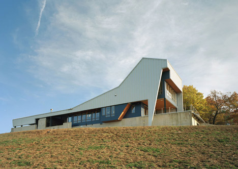 Angular metal roof wraps around a hilltop house by deMx architecture