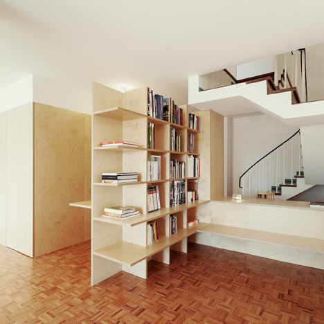 Wooden structures combine partitions and<br /> furniture inside home by João Branco