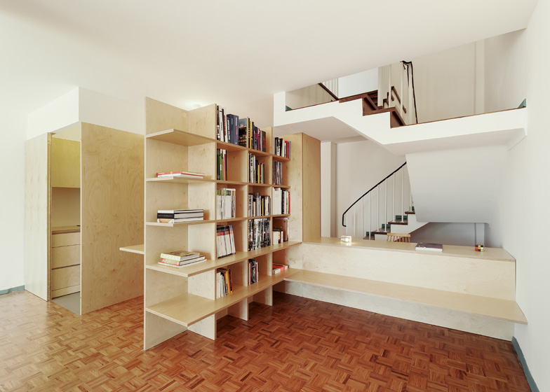 Wooden structures combine partitions and furniture inside home by João Branco