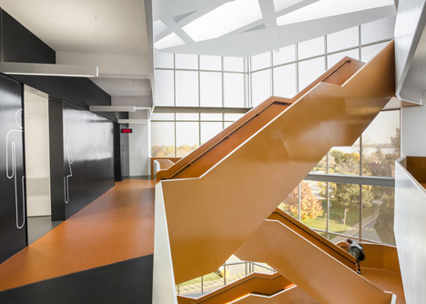Grand orange staircase ascends through college by Saucier + Perrotte