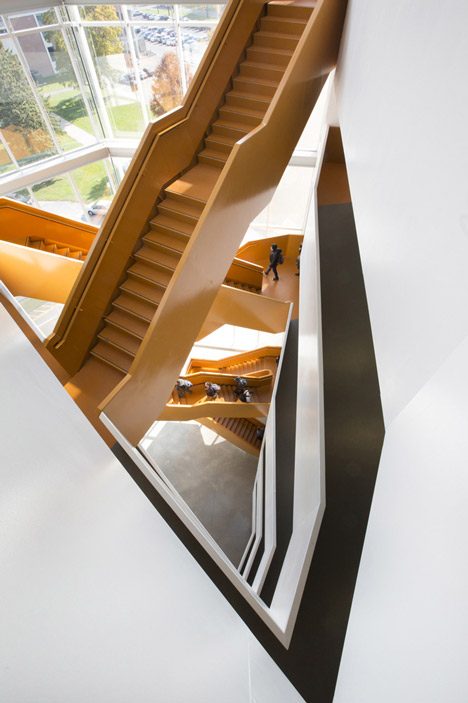 Grand orange staircase ascends through college by Saucier + Perrotte