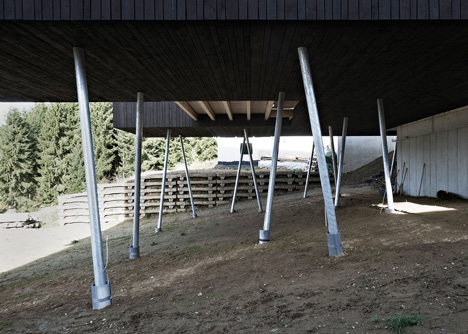 Black-painted S House by Hammerschmid Pachl Seebacher raised up on stilts
