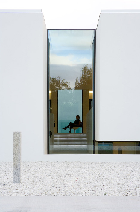 Doorway hidden in volcanic stone wall of B25 house by PK Arkitektar