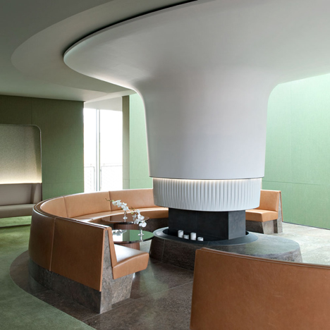 Nature-inspired hotel lounge by Jouin Manku features an organic fireplace