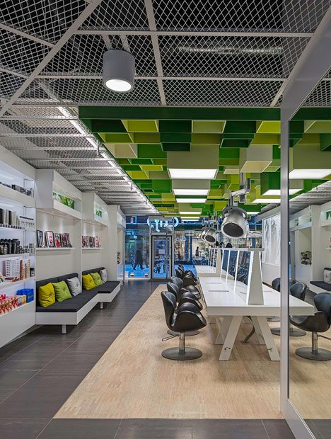 Green boxes cover the ceiling of Clip Drop In hair salon by Sweco Architects