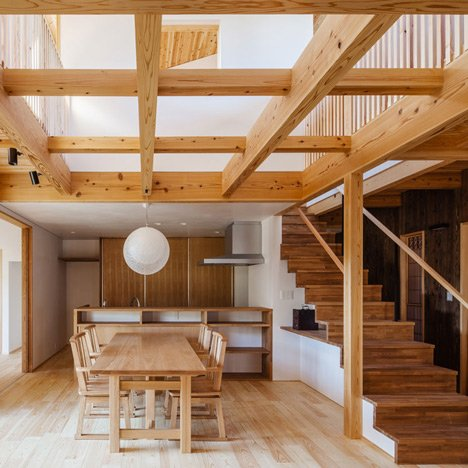 Criss-crossing wooden beams fill a void inside Studio Aula's Cocoon House