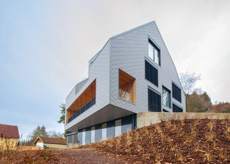 House B.A.B.E. by Destilat features windows dotted across shingle-clad facade