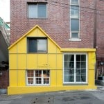 Yellow house-shaped facade fronts cafe by Nordic Bros Design Community