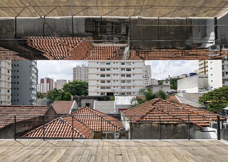 Shiny metal box hovers above shopping and restaurant complex by Triptyque