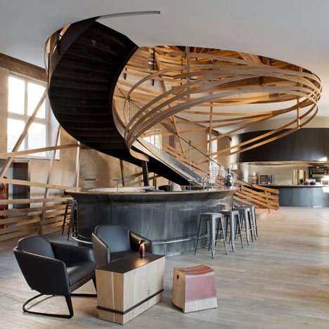 Wooden strips coil around staircase at Strasbourg hotel by Jouin Manku