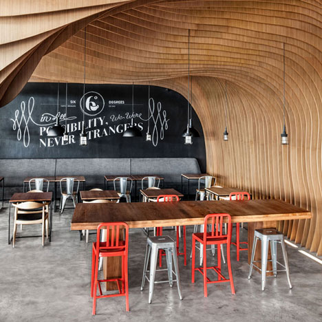 OOZN Design creates cavernous cafe in Jakarta using undulating timber slats