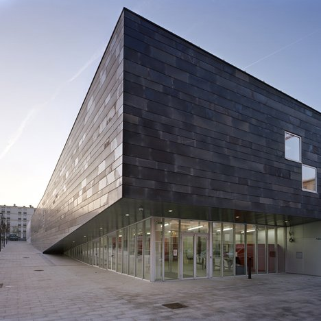 Parisian suburb gets monolithic, tilting sports centre with basalt facade