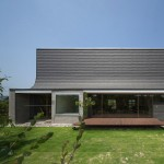Curving roofline enhances acoustics inside house with a music hall by NKS Architects