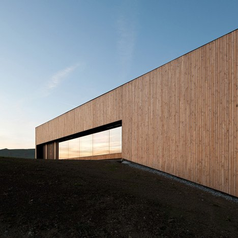 Timber walls feature narrow vertical slices<br /> at Virdis Architecture's Lussy Sports Hall