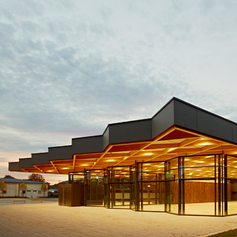 Criss-crossing timber canopy extends over Ackermann + Raff's glass-fronted festival hall