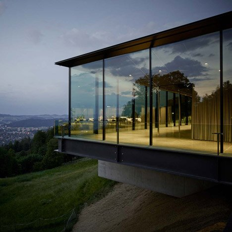 Alpine events venue by MLZD features glass walls with golden outdoor curtains