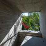 Concrete tunnel extends through an old stone wall at Leyva 506 house by APT