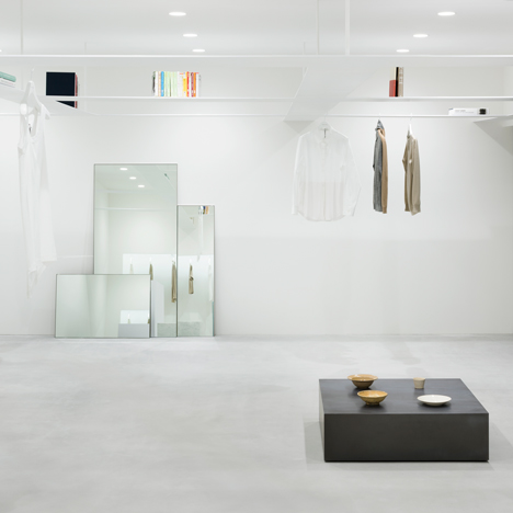 Nendo's grid of suspended bookshelves hangs above shoppers in Beige fashion boutique