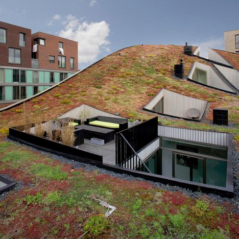 Terraces are cut out of the curved green roof of NL Architects' Funen Blok K