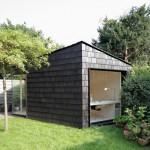 Garden studio by Serge Schoemaker has a dark, rough exterior and a light-filled interior