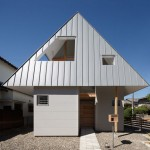 Overhanging roof forms a hood over Japanese house by Moca Architects