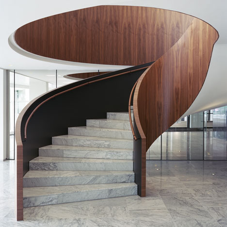 Powerhouse Company remodels office foyer in marble and dark wood to resemble a hotel lobby