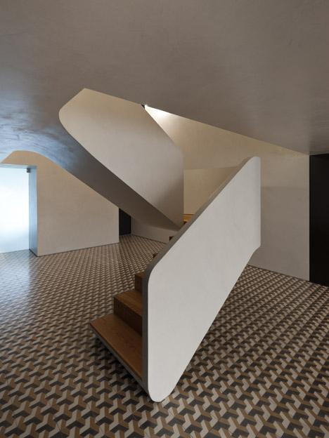 Correia/Ragazzi Arquitectos add curving white staircase to a remodelled Portuguese apartment