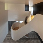 Correia/Ragazzi Arquitectos add curving white staircase to a remodelled Portuguese apartment