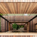 A tree grows up through voids in Hamada Design's Glass + Wood building