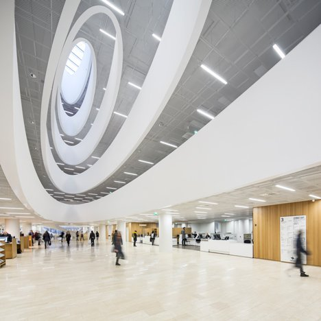 Curving voids pierce the floors of Anttinen Oiva Architects' Helsinki library