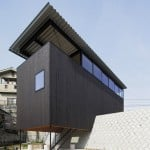 Yoshio Ohno's black timber house straddles a concrete escarpment in Hiroshima